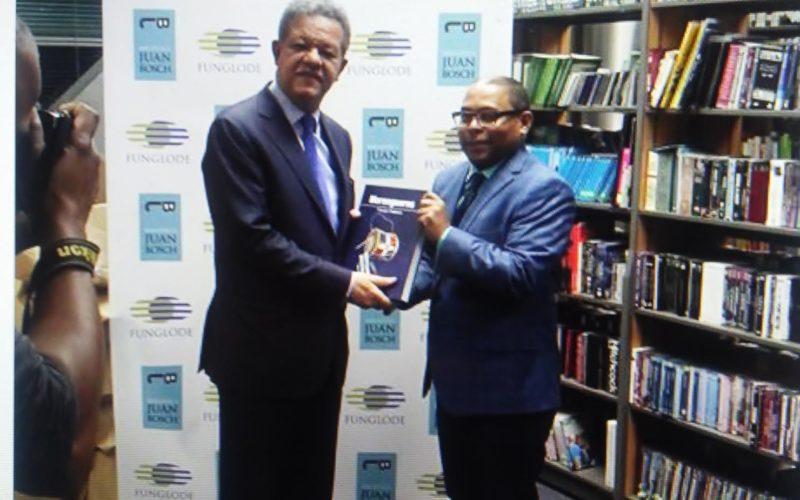 Leonel recibe un ejemplar del libro «Merengueros» de manos de su autor Fausto Polanco
